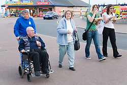 Wheel chair user and wife being helped by a friend whilst on a day trip to Skegness organised by Nottingham Disabled Friendship Club,