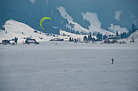 A kite boarder enjoying himself on a frozen lake on a Swiss winter day.