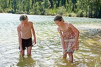 Two girls (7-9) standing in lake playing.