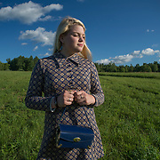 A 17-year-old blond haired teenager wearing a 1960s plaid dress, stands facing the evening sun. Her eyes are closed and she is holding a blue, antique purse.