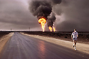 An avid runner not deterred by disaster, Dr. Daoud, head of preventive services at Ahmadi Hospital takes his daily jog near the burning Kuwait oil fields. (May, 1991). Dr. Daoud, a Palestinian doctor working in Kuwait for many years, participated in studies of the effects of breathing oil well fire smoke for extended periods of time by dissecting the lungs of sheep kept alive in Kuwait and comparing them with imported sheep. He displayed some of the healthy and diseased lungs.