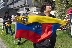April 30, 2019 - A woman holds a Venezuelan flag in front of the consulate in Bogota because of the crisis in her country and in support of the interim president, Juan Guaido (Credit Image: © Daniel Garzon Herazo/ZUMA Wire)