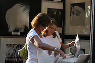 Two women sort through art photos of horses at St. Louis Art Fair, renowned for its high-end works in all media; Clayton, Missouri.