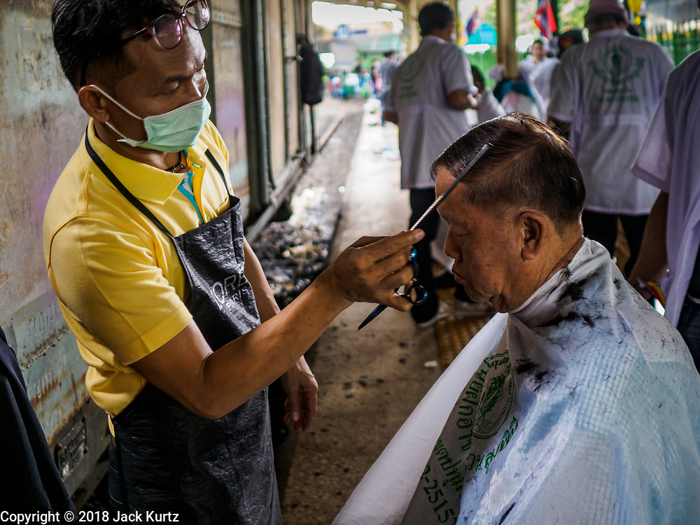 12 SEPTEMBER 2018 - BANGKOK, THAILAND: A barber checks his work on a traveler at Hua Lamphong train station in Bangkok. Barber schools set up in the station and offer free haircuts to travelers.    PHOTO BY JACK KURTZ
