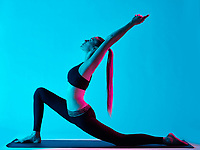 one caucasian woman exercising Anjaneyasana yoga exercices  in silhouette studio isolated on blue background