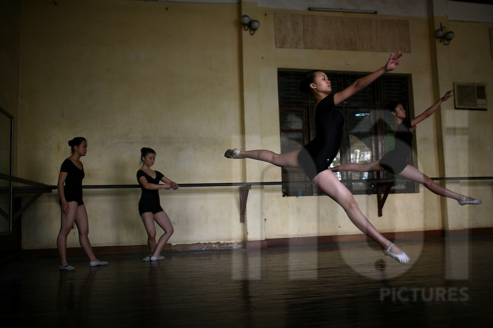 Young Vietnamese ballet dancers leap across the floor of a Hanoi ballet studio, Vietnam, Southeast Asia