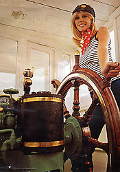 """© Licensed to London News Pictures. 04/05/2016. Birkenhead UK. Collect picture shows model's posing on the Daniel Adamson for a Shell Oil company calendar in the 1970's. The Daniel Adamson steam boat has been bought back to operational service after a £5M restoration. The coal fired steam tug is the last surviving steam powered tug built on the Mersey and is believed to be the oldest operational Mersey built ship in the world. The """"Danny"""" (originally named the Ralph Brocklebank) was built at Camel Laird ship yard in Birkenhead & launched in 1903. She worked the canal's & carried passengers across the Mersey & during WW1 had a stint working for the Royal Navy in Liverpool. The """"Danny"""" was refitted in the 30's in an art deco style. Withdrawn from service in 1984 by 2014 she was due for scrapping until Mersey tug skipper Dan Cross bought her for £1 and the campaign to save her was underway. Photo credit: Andrew McCaren/LNP ** More information available here http://tinyurl.com/jsucxaq **"""