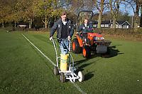 BLOEMENDAAL - Hockey op ECHT gras. Jules Hustinx, Clubmanager van HC Bloemendaal trekt de lijnen. Hidde Maas (r)  maait  het gras. COPYRIGHT KOEN SUYK