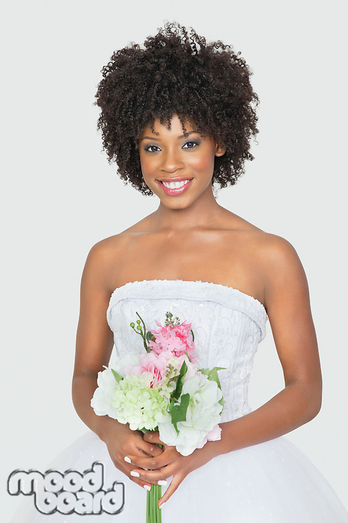 Portrait of an attractive African American bride holding bouquet over gray background