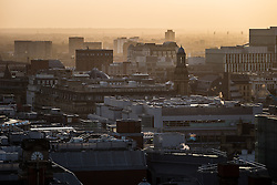 © Licensed to London News Pictures . 14/11/2013 . A boiling orange winter sunset above Manchester City Centre this evening (14th November 2013) . In the distance on the right of the frame are the lights of Old Trafford (Manchester United FC stadium) . Photo credit : Joel Goodman/LNP