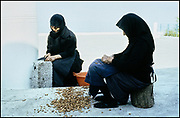 Greek ladies in black cracking almonds on a terrace in Samaria, Crete, Greece