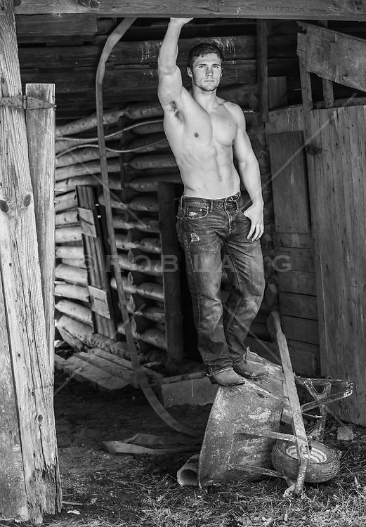 shirtless man in an run down barn
