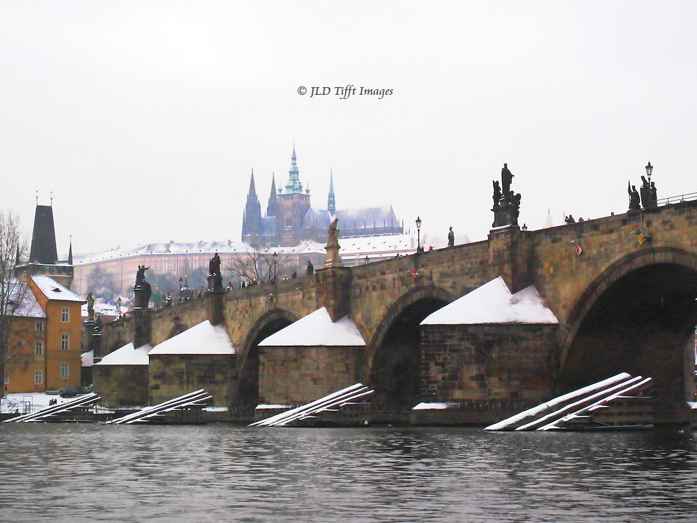 On a winter day, the medieval Charles bridge and its abutments are covered with snow.  View from a boat in the river near the bridge, looking up past it to the cathedral on its hill above.  Cold weather, white sky, gray river water.