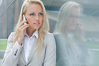 Beautiful young businesswoman conversing on cell phone while looking away by glass wall
