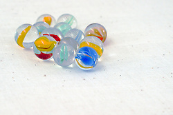25 July 2006 toy glass marbles shot in a light tent on a fabric background .