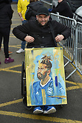 A Birmingham City fan poses with an oil painting of Birmingham City midfielder Jacques Maghoma (19)  during the EFL Sky Bet Championship match between Birmingham City and Aston Villa at St Andrews, Birmingham, England on 10 March 2019.