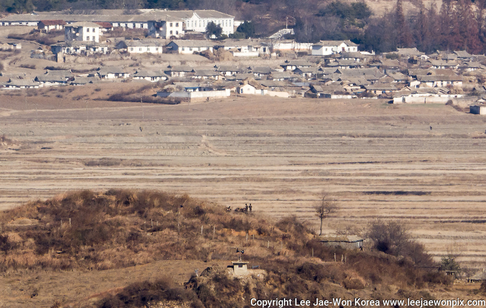 North Korean soldiers (C) talk at a border village in Kaepung county, North Hwanghae province, in this picture taken from Ganghwa Peace Observatory of South Korea, about 2 km (1.2 miles) south of the North Korean territory, in Ganghwa, 56 km (35 miles) northwest of Seoul, South Korea, Dec 4, 2017. Photo by Lee Jae-Won (KOREA) www.leejaewonpix.com