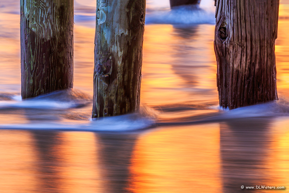 Sunrise reflected in the moving water under Avalon fishing Pier on the Outer Banks.