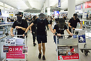 CHINA, Hong Kong: 13 August 2019 <br /> Demonstrators bring luggage trollies to help build a barricade during clashes with riot police at Hong Kong International Airport on the evening of 13th August 2019. Thousands of demonstrators brought Hong Kong's airport to a standstill for a second day in a row in protest of the extradition bill as well as the police violence and brutality. Demonstrators have taken to the streets of Hong Kong in protest of a controversial extradition bill since 9th of June which has resulted in several violent clashes.<br /> Rick Findler / Story Picture Agency
