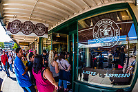 People line up outside the original store of Starbucks in Pike Place Market, Seattle, Washington USA.