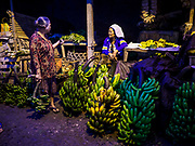 04 AUGUST 2017 - PAYANGAN, BALI, INDONESIA: A customer buying bananas in the local market in Payangan, about 45 minutes from Ubud. Bali's local markets are open on an every three day rotating schedule because venders travel from town to town. Before modern refrigeration and convenience stores became common place on Bali, markets were thriving community gatherings. Fewer people shop at markets now as more and more consumers go to convenience stores and more families have refrigerators.      PHOTO BY JACK KURTZ