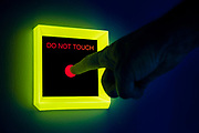 A finger touches a red button on a Do Not Touch sign. Blacklight Photography