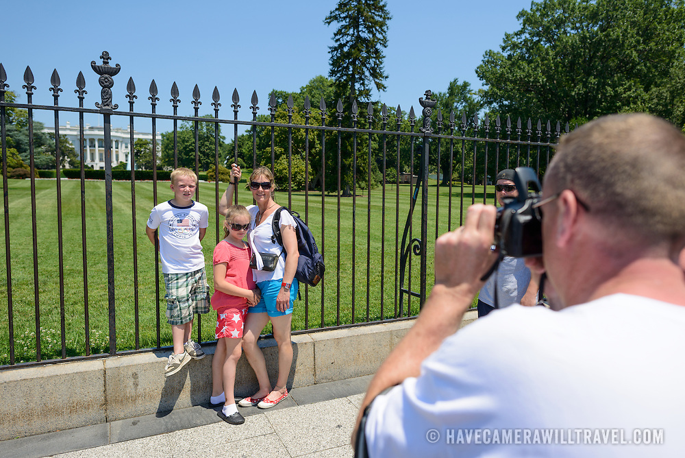 White House Tourist Family Posing for Photos. Tourists pose for photos in front of the southern side of the White House in Washington DC.