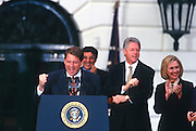 US President Bill Clinton and First Lady Hillary Clinton watch as Vice President Al Gore address the White House staff during a welcome home ceremony after winning re-election at the White House November 6, 1996 in Washington, DC.