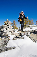 A woman hiking past a trail marker, Enchantment Lakes Wilderness Area, Washington Cascades, USA.