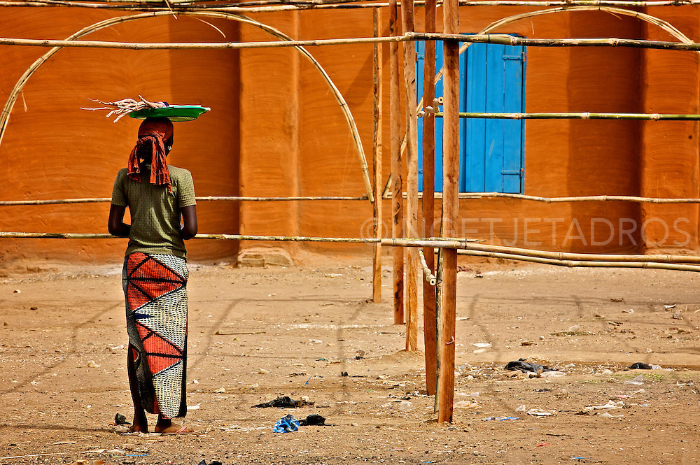 Woman watching the beginning of the set up of a market in Segou, Mali, 2009<br />