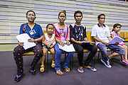 "17 JULY 2014 - BANGKOK, THAILAND: Undocumented Cambodian migrant workers wait to be called for ID cards at the temporary ""one stop service center"" in the Bangkok Youth Center in central Bangkok. Thai immigration officials have opened several temporary ""one stop service centers"" in Bangkok to register undocumented immigrants and issue them temporary ID cards and work permits. The temporary centers will be open until August 14.    PHOTO BY JACK KURTZ"