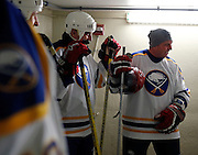 Matthew Barnaby, right, and other members of the Sabres alumni team share stories from their playing days before the Amerks vs. Sabres alumni game at Frontier Field in Rochester on Sunday, December 15, 2013.