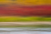 A long exposure and intentional camera movement combine to create a sense of color in motion from the Deschutes River flowing by bands of multi-hued autumn foliage on its banks.