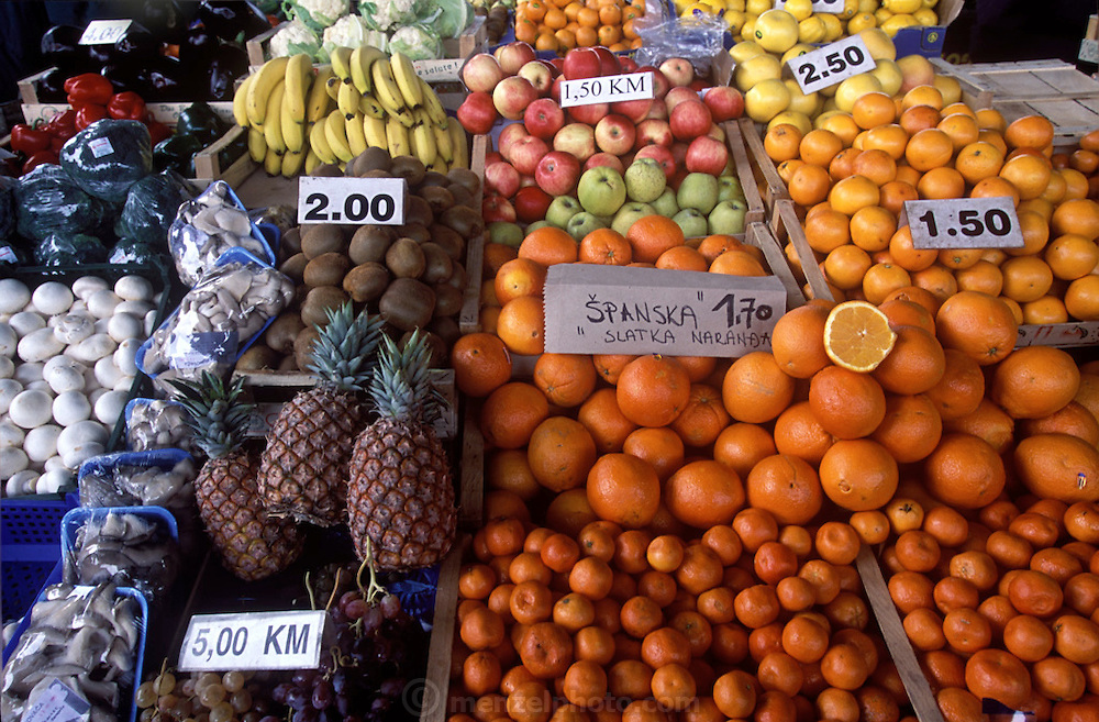 "Fruits and vegetables for sale at the outdoor ""green"" Ciglane market in Sarajevo in Bosnia and Herzegovina. Signs of the four-year siege of Sarajevo are still obvious today. Although food stalls have returned to the Ciglane market, parts of the Olympic park behind it have become a burial ground for siege victims. (Supporting image from the project Hungry Planet: What the World Eats.)"