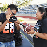 Freshman Stephon Smith and senior Judith Duboise pump up a football to get ready for Friday night's Gallup Bengal varsity football home opener.