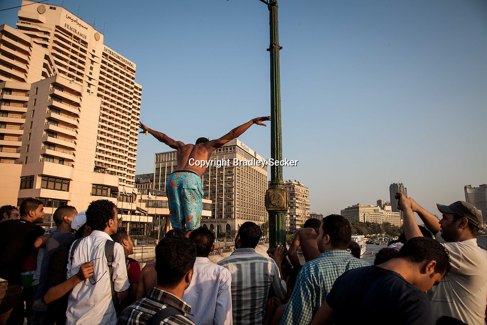 After hearing of president Morsi's arrest, a man jumps into the river Nile as a crows watches.