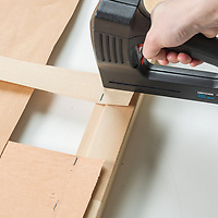 Stapling wood veneer strips to headboard frame