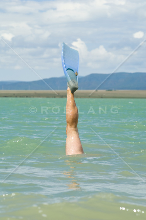Man's leg with a blue flipper sticking up out of a blue lake In New Mexico