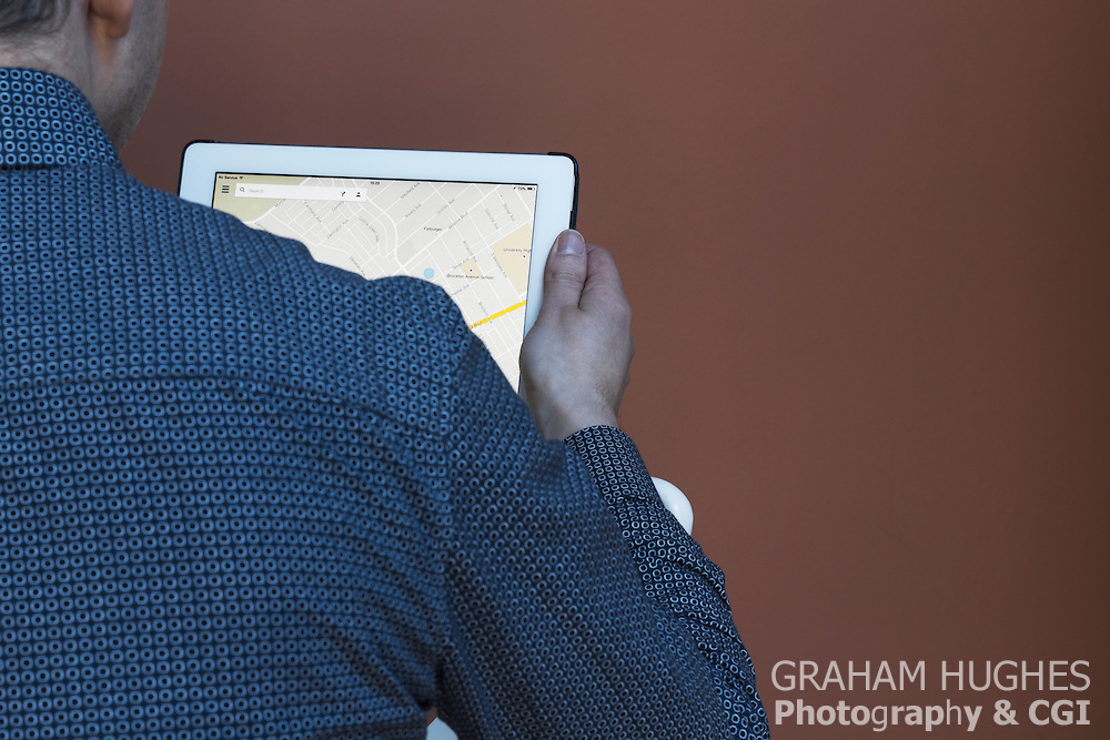 Male using iPad 2 with Google maps on screen.