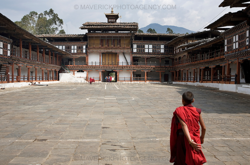 A young monk walks across the courtyard of Wangdiphodrang dzong , Wangdiphodrang..Commonly described as the last Himalayan Shangrila, Bhutan is a country of unique serenity, harmony, and beauty. Nestled between India, China, and Tibet, this independent country whose name translates as 'the Land of the Thunder Dragon' has for the past 300 years  proactively followed a policy of isolation and cultural protection. Travel in and out of the country is strictly regulated, and the impact of outside influences on the local culture is carefully monitored. Spirituality is an important aspect of Bhutanese culture, with Buddhism being interlinked with everyday life. Gross National Happiness (GNH), as opposed to GNP/GDP, forms the cornerstone of its development strategy which focuses on a holistic development strategy that complements its cultural and Buddhist spiritual values. .