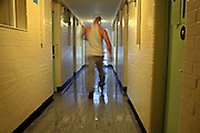 A prisoner walks down the third level of C wing at Coldingley prison, he is returning to his cell after work..HMP Coldingley, Surrey was built in 1969 and is a Category C training prison. Coldingley is focused on the resettlement of prisoners and all prisoners must work a full working week within the prison. Its capacity is 390 prisoners.