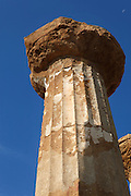 Detail of column with capital, Temple of Hercules,  Agrigento, Sicily, Italy,  pictured on September 12, 2009, in the morning. The date of the Temple of Hercules is uncertain; although the style indicates late 6th century BC,  its entablature is mid 5th century. It was built with a peristasis of 6 x 15  tall Doric columns with wide capitals, and a cella with pronaos and opysthodomus, above a three-step basement.  8 columns and an altar have survived the earthquake which destroyed the temple. The Valley of the Temples is a UNESCO World Heritage Site. Picture by Manuel Cohen.