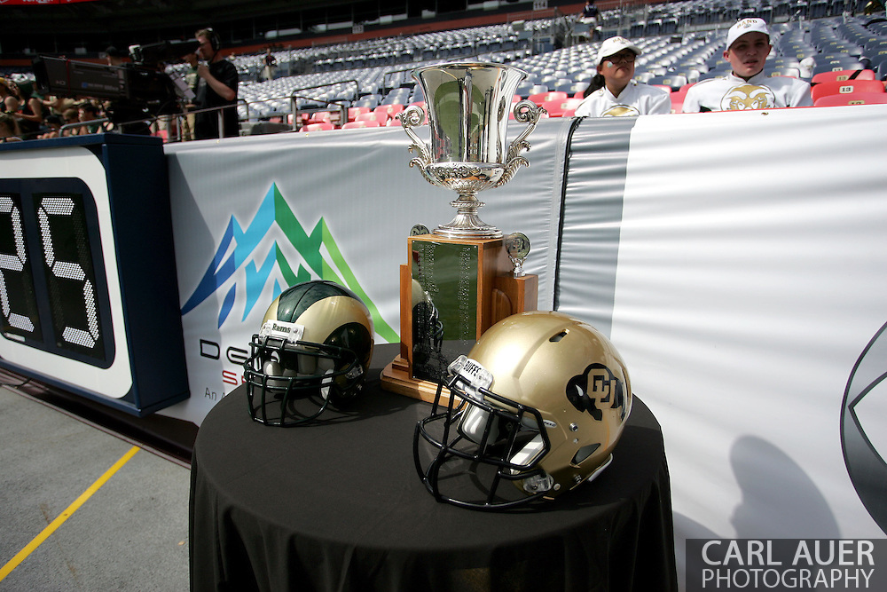 September 1st, 2013 - The trophy for the Rocky Mountain Showdown sits between the helmets of the Colorado Buffaloes and the Colorado State Rams prior to the start of the NCAA football game at Sports Authority Field in Denver, CO