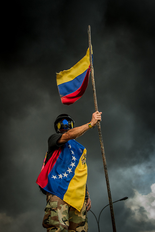 """CARACAS, VENEZUELA - MAY 27, 2017:  An anti-government protester of """"The Resistance""""  during a lull in fighting as an industrial sized truck that protesters highjacked and used as a roadblock after taking over the main highway that runs through Caracas, burns in the background.  The streets of Caracas and other cities across Venezuela have been filled with tens of thousands of demonstrators for nearly 100 days of massive protests, held since April 1st. Protesters are enraged at the government for becoming an increasingly repressive, authoritarian regime that has delayed elections, used armed government loyalist to threaten dissidents, called for the Constitution to be re-written to favor them, jailed and tortured protesters and members of the political opposition, and whose corruption and failed economic policy has caused the current economic crisis that has led to widespread food and medicine shortages across the country.  Independent local media report nearly 100 people have been killed during protests and protest-related riots and looting.  The government currently only officially reports 75 deaths.  Over 2,000 people have been injured, and over 3,000 protesters have been detained by authorities.  PHOTO: Meridith Kohut"""