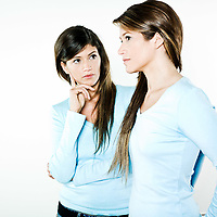 studio shot portrait on isolated background of two sisters twin women friends looking at the other as it was herself