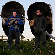 16/05/2016 <br /> Fishermen Malcolm Rees and David Elias pose for a portrait with their Coracle fishing boats near the River Towy in Carmarthenshire, west Wales. <br /> The Coracle fishing with nets by hand is a tradition that has been passed through families from generation to generation for hundreds, if not thousands of years. The Coracle is a shallow one person boat which is used for fishing sea trout and sea salmon in pairs. Coracle fishermen fish by night so as not to disturb fish. They wait until seven stars are in the sky, by which time it is deemed dark enough to fish.<br /> There are only eight licences to fish on the River Towy and a handful of others in other Welsh rivers. With dwindling trout and salmon stocks the Environment Agency is thought to be planning to heavily restrict catches to the point that 2016 may the last fishing season in it's current traditional form. As it is times are hard and a pair of coracle fishermen are lucky to catch any fish on a run - when they do, they can expect to sell a trout for around &pound;30.00.<br /> <br /> <br /> Neil Hall Photography Ltd<br /> www.neilhallphotography.com<br /> 07766227770<br /> 3 Crown Court<br /> Crown Road<br /> London<br /> N10 2JA