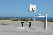 two boys playing with a basketball