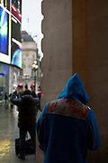 A man wearing a distinctive hooded coat takes shelter under the arches outside Piccadilly Circus underground station, on 12th November 2019, in London, England.