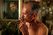 Alejandro Ferras Pellicer, 84, who claims to have been an original revolutionary in Fidel Castro's army at  the time of the communist overthrow of Cuba, smokes a cigar while taking a break from the ongoing renovation of a house he says once belonged to Che Guevara. Behind him is a poster of Fidel Castro, on May 4, 2005.
