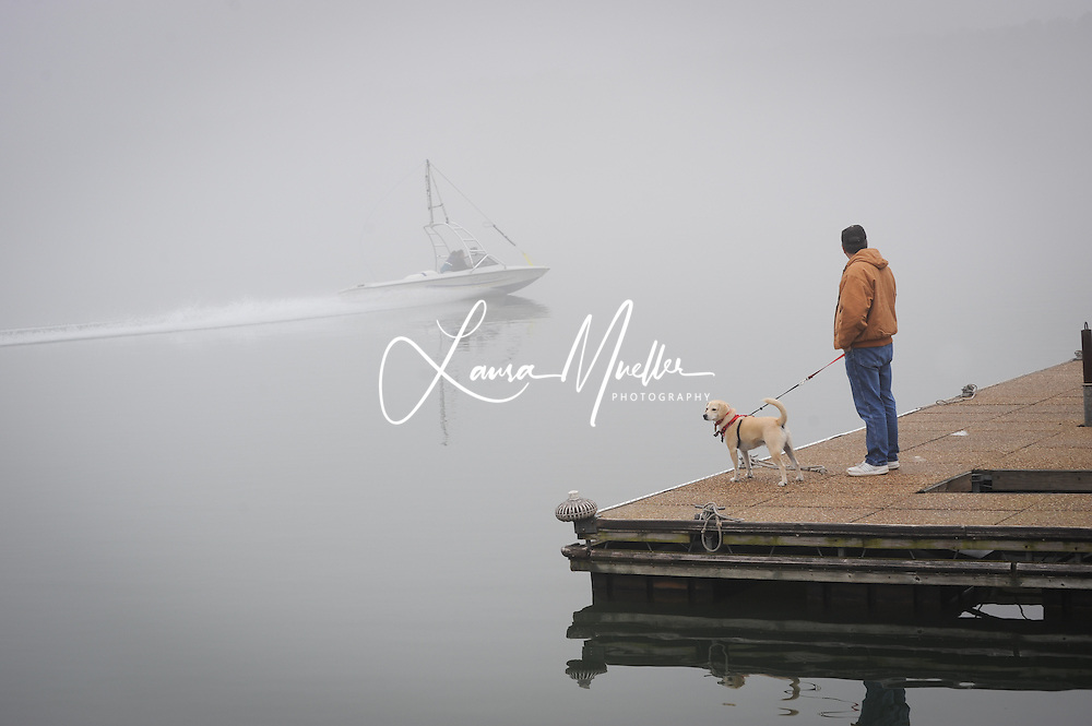 Sherrills Ford, NC - Charlie Glassey of Terrell and his dog Hotrod watch from the Lake Norman Marina dock as the towboat makes a test run in the morning fog prior to the 33rd Annual Lake Norman New Years Day Barefoot Challenge. <br /> photo &copy; Laura Mueller - www.lauramuellerphotography.com